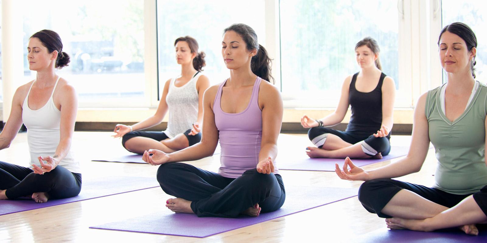 mujeres sentadas con las piernas cruzadas y los ojos cerrados sobre tapetes de yoga