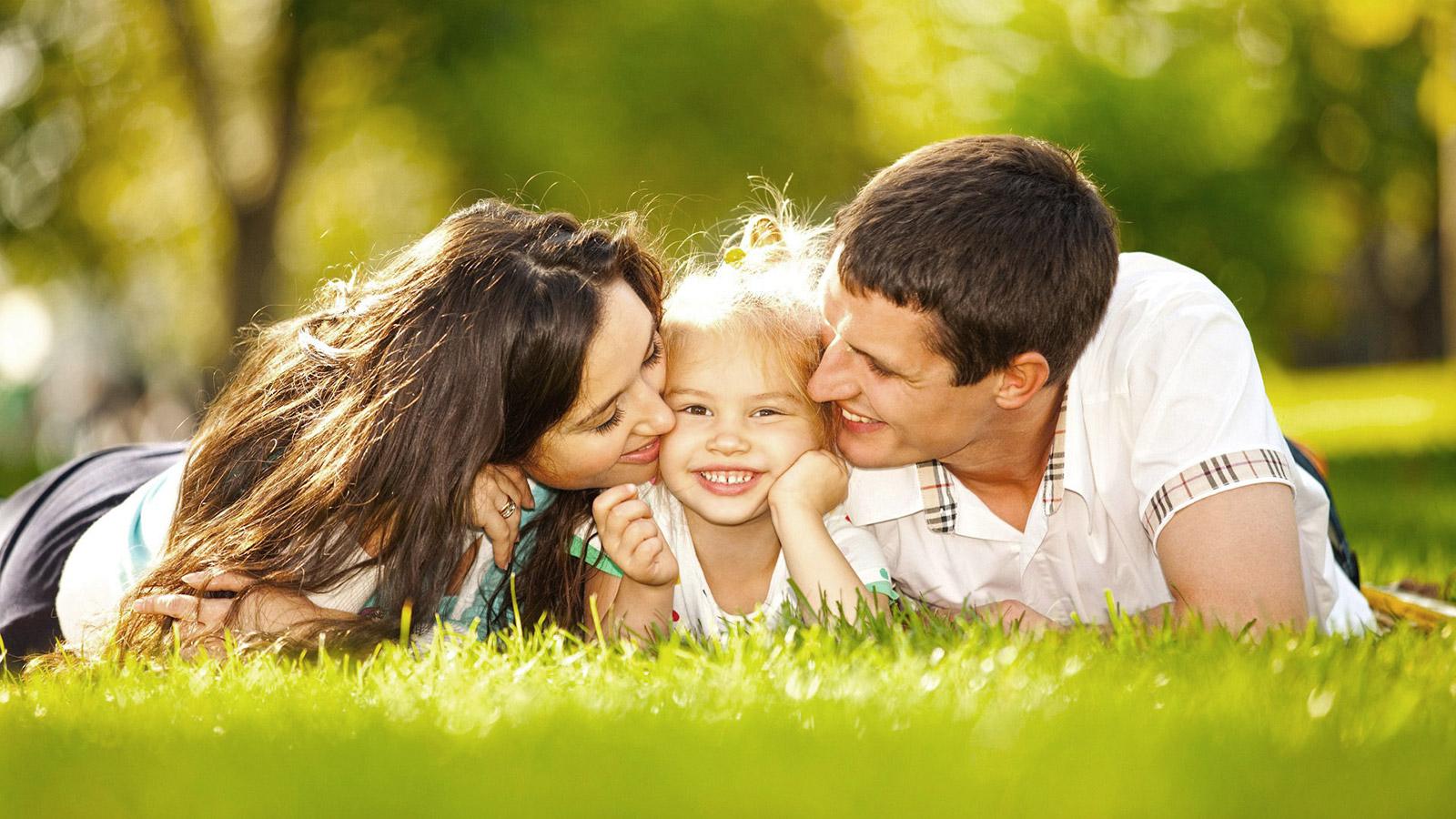 padres besando las mejillas de su hija acostados bocabajo sobre el cesped