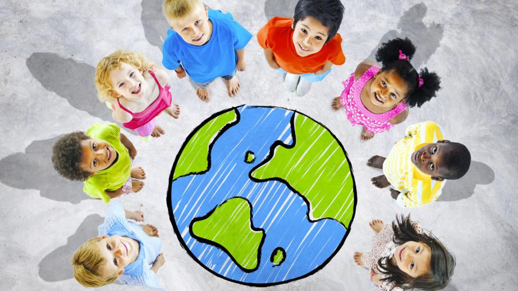 niños volteando hacia arriba parados alrededor de un mundo pintado en el suelo